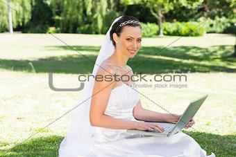 Smiling bride using laptop in garden