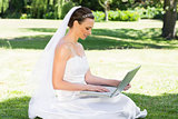 Attractive bride using laptop in garden