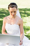 Bride using laptop in garden