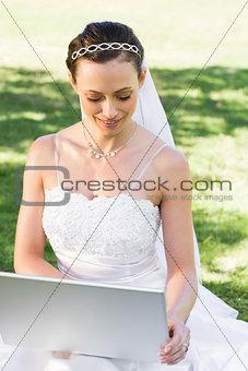 Bride using laptop in garden