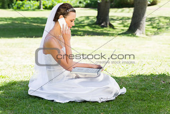 Bride using laptop and mobile phone in park