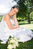 Happy bride sitting on grass in garden