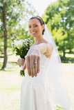 Bride showing wedding ring in garden