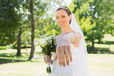 Beautiful bride showing wedding ring in garden