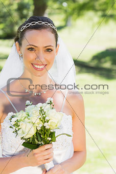 Bride smiling while holding flower in garden