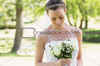 Bride looking at bouquet in garden