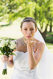 Bride with bouquet blowing kiss in garden