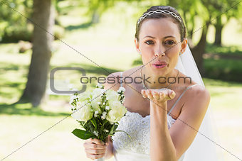 Beautiful bride with bouquet blowing kiss in garden