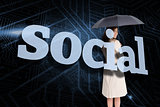Businesswoman holding umbrella behind the word social