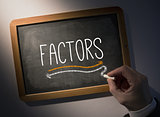 Hand writing Factors on chalkboard