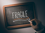 Hand writing Fragile on chalkboard