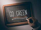 Hand writing go green on chalkboard