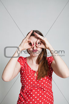 Attractive woman looking through finger goggles