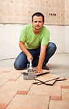 Man cutting ceramic floor tiles