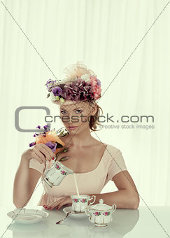 blonde girl with classical tea set takes milk jug