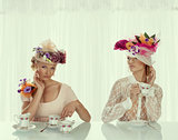 two blonde girl with classical tea set takes tea cup