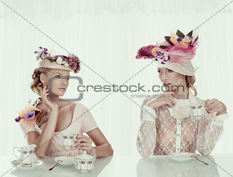 blonde girls with classical tea set and flower hat