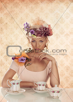 blonde girl with classical tea set and hand under the chin