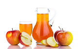 Fresh red apples, glass with juice and carafe