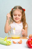Girl playing in a cook churn whisk eggs glass bowl