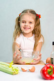 Girl playing a cook churn whisk eggs in glass bowl