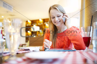 Woman in cafe with touchpad and phone