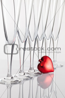 Six glasses of champagne and red heart on a glass table