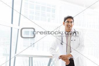 Smiling Asian Indian male medical doctor inside hospital.