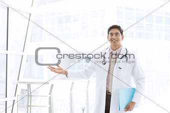 Asian Indian male medical doctor showing welcome hand sign