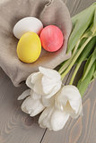 pastel color easter eggs with tulips on table