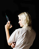 Beautiful young girl in the image of nurse with syringe in hand, rear view