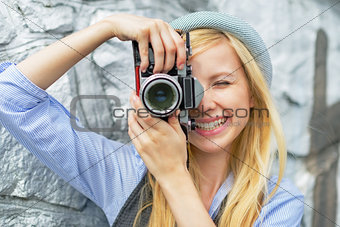 Portrait of young hipster taking photo with retro photo camera
