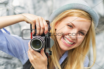 Portrait of smiling young hipster with retro photo camera