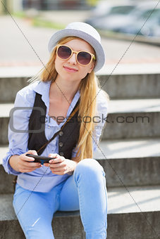 Portrait of young hipster sitting on bench in the city