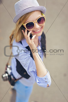 Young hipster talking cell phone on city street