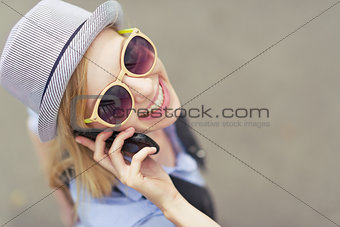 Portrait of happy young hipster talking cell phone on city stree