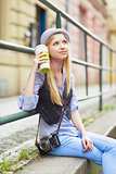 Young hipster sitting in the city with cup of hot beverage