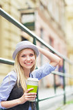 Young hipster enjoying cup of hot beverage in the city