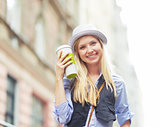 Happy young hipster with cup of hot beverage in the city