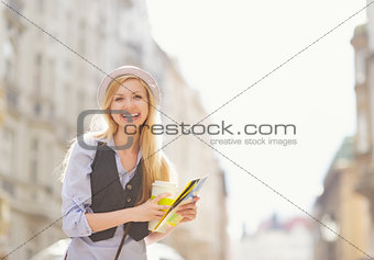 Happy young woman tourist with map in the city