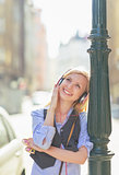 Happy young woman listening music in headphones in the city