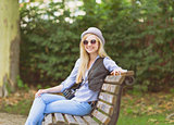 Young hipster sitting on bench in the park
