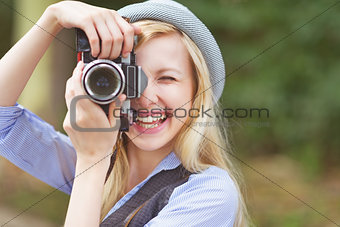 Happy young hipster taking photo with retro photo camera sitting