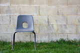 Abandoned chair in front of a concrete block wall