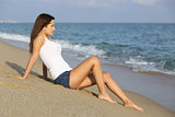 Beautiful woman sitting on the sand of the beach watching the sea