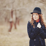 Spring portrait of red hair girl in hat and coat.