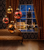 Christmas balls in room, town view window