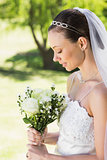 Shy bride holding bouquet in garden