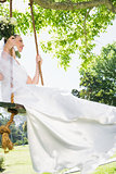 Thoughtful bride swinging in garden