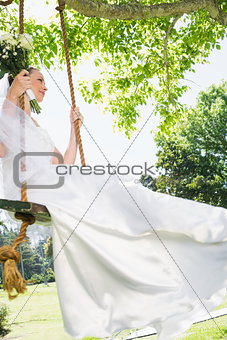 Thoughtful bride swinging in garden